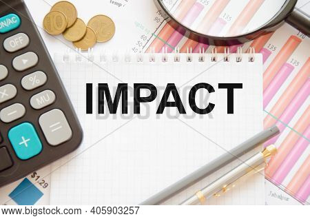 The Word Impact Is Written On A White Notepad On Pink Graphics Near A Calculator, Coins, Pens, Magni