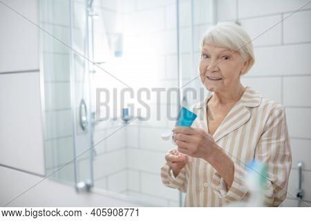Elderly Woman Doing Morning Procedures In The Bathroom