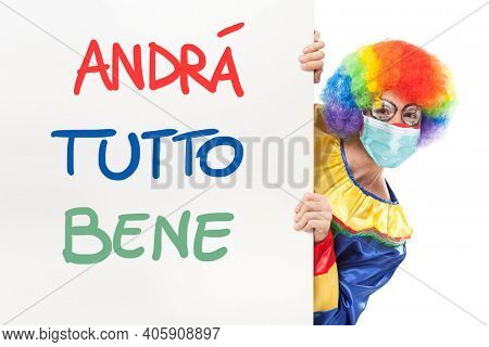 Clown wearing a mask showing a panel with the italian text Andrà tutto bene, which means Everything will be alright. Coronavirus concept