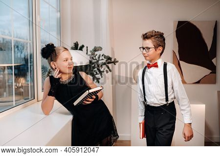 Stylish Boy And Girl Stand Near The Window With Books In Their Hands