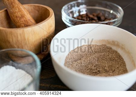 Group of bowls with wooden pounder, glassware with coffee beans and titanium dioxide powder and other ingredients for making soap