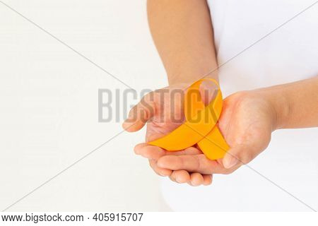 Hands Holding Orange Color Ribbon On White Fabric With Copy Space. Kidney Cancer Awareness, Leukemia