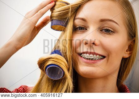 Hair Styling At Home Concept. Woman Curling Her Hair Using Rollers In Bathroom
