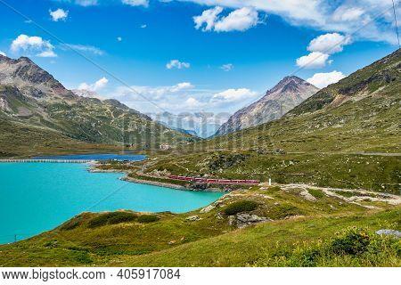 Bernina Express Train At The White Lake In Ospizio Bernina, Upper Engadin, Graubuenden, Grisons, Swi