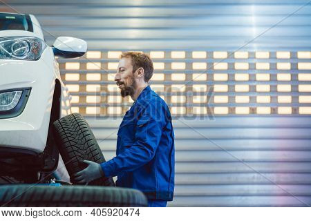 Car mechanic changing tire in his workshop lifting the wheel