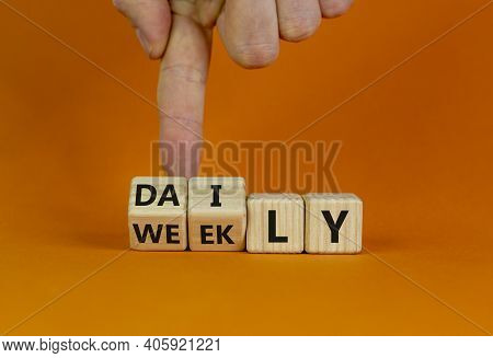Daily Or Weekly Symbol. Businessman Flips Wooden Cubes And Changes The Word 'weekly' To 'daily'. Bea