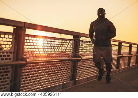 Young Happy African-american Man Is Jogging On The Bridge In The City. He Is Exercising To Reduce Hi