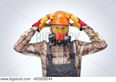 Close-up Portrait Of A Builder With Protective Glasses, Respirator And Helmet Indoors. Personal Prot