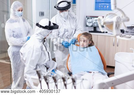 Little Girl Looking At Dentist While Assistant Is Putting Her A Bib Before Dental Examination Uring