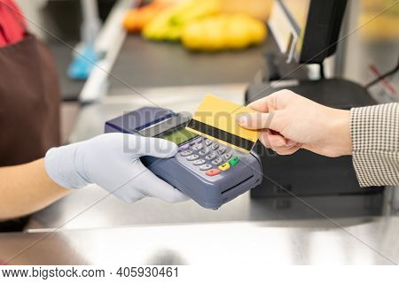 Hand of young female cashier in uniform and protective gloves holding payment terminal while one of consumers paying by credit card