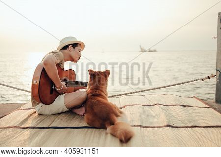 A Man Wear Straw Hat And Playing Guitar Music Song Near The Sea Sunset And Him Need Kiss With A Dog