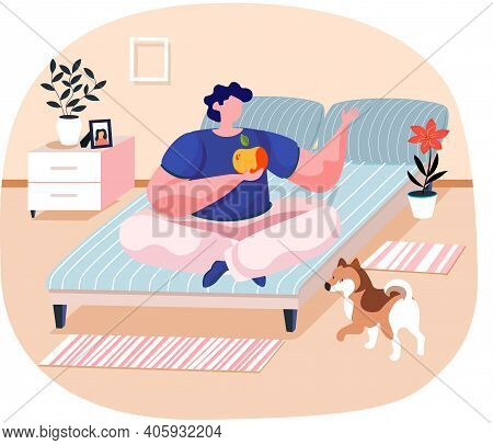 Pet Owner Young Man Sitting On Bed In Bedroom On Lotus Position Holding An Apple With Cute Dog. Male