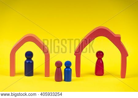Wooden Figures, Miniature People Standing Inside Of Houses And Children Between Them On Yellow Backg