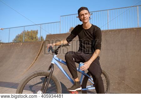 Young male bmx biker leisures on ramp in skatepark