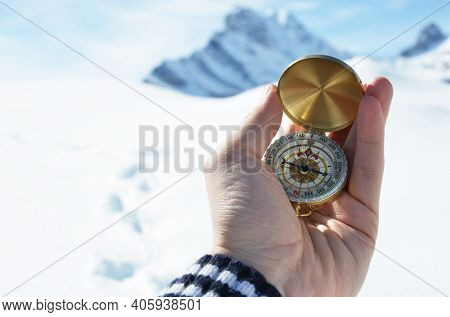 Compass in the hand against snowy mountains