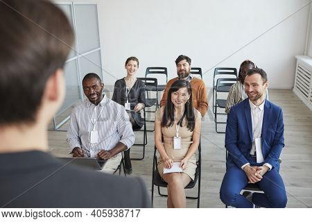 High Angle View At Multi-ethnic Group Of Business People Looking At Coach And Smiling While Sitting