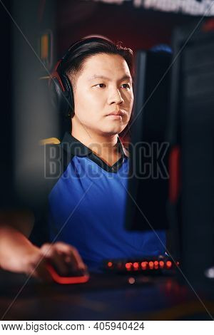 Vertical Shot Of Concentrated Asian Guy, Male Cyber Sport Gamer Wearing Headphones Looking At Pc Scr