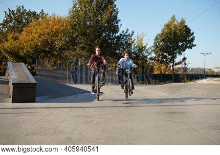 Young bmx bikers doing tricks in skatepark