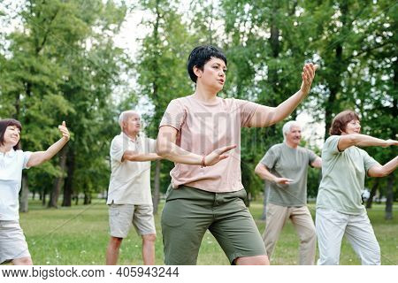 Group of mature people doing exercises with trainer in the park outdoors