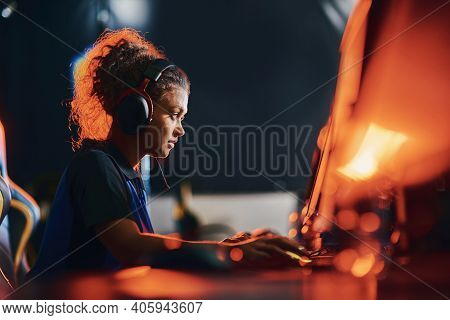 Side View Of A Young Mixed Race Girl, Female Cybersport Gamer Wearing Headphones Playing Online Vide