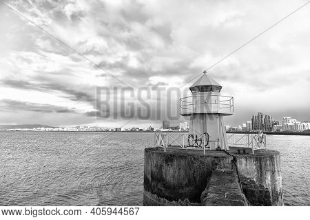 Lighthouse On Sea Pier In Reykjavik Iceland. Lighthouse Yellow Bright Tower At Sea Shore. Sea Port N