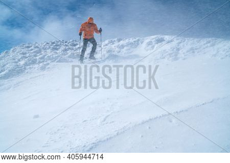 High Mountaineer Dressed Bright Orange Softshell Jacket Using A Trekking Poles Descending The Snowy