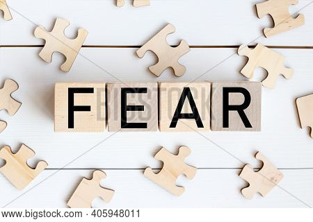Word Fear On Wooden Blocks, Over White Background. Psychology Of Fear. Fold The Puzzle. Causes Of Fe