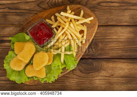 Delicious Crispy Fried Chicken Nuggets And French Fries Close-up With Sauce On The Board. A Bunch Of