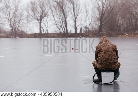 Fisherman From The Back Catching Fish In The Ice Hole On The Frozen Lake. Man Fishing In Winter. Win