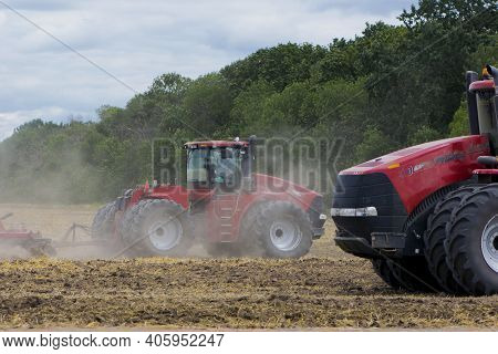 Two Red Tractors, Work In The Field On A Large Tractor, Harvesting, Agriculture. Two Red Tractors In