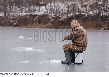 Fisherman Catching Fish In The Ice Hole On The Frozen Lake. Man Fishing In Winter. Winter Fishing Co