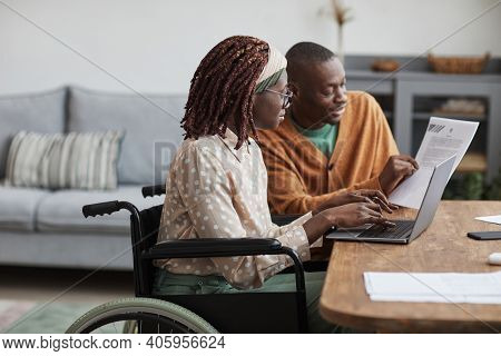 Side View Portrait Of Young African-american Woman Using Wheelchair Working From Home With Husband H