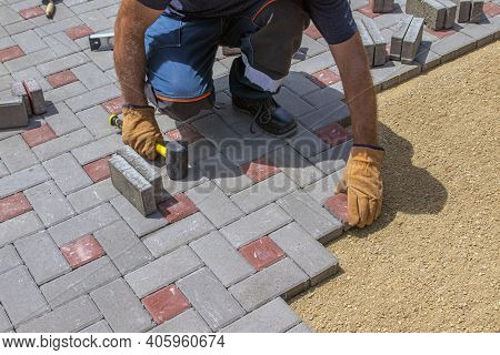 A Gloved Craftsman Lays Down The Paving Stones In Layers. Laying Gray Concrete Paving Slabs In The C