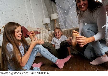 Mom And Kids Have Fun In The Bedroom And Tickle Each Others Feet. The Older Sister Helps Tickle The