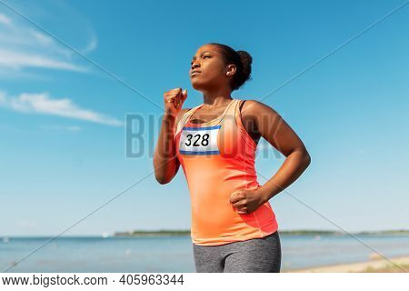 fitness, sport and race concept - young african american woman running marathon with badge number on shirt