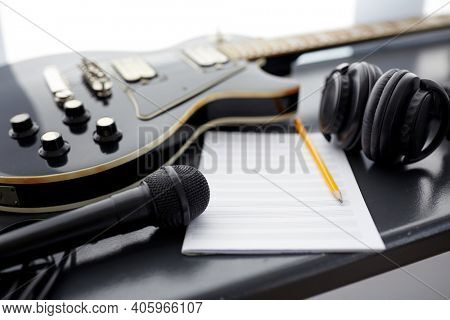 composing and music writing concept - close up of bass guitar with music book, microphone and headphones on black table