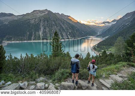 Olpererhutte, Austria - Aug 7, 2020: Two Female Trekkers Take Photo Of Glacier Reservoir At Sunset H