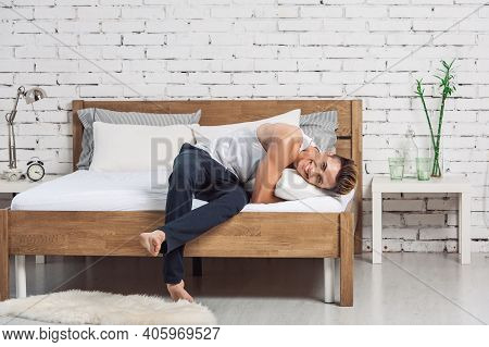 Smiling Man Lying On A White Pillow And A Mattress On A Wooden Bed. Concept Of Comfortable Sleep. Or