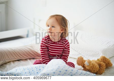 Happy Toddler Girl In Striped Red And White Pajamas Sitting On Bed Right After Awaking. Day Naps For
