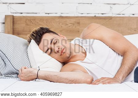 Man Sleeping On A White Pillow And A Mattress On A Wooden Bed. Concept Of Comfortable Sleep. Orthope