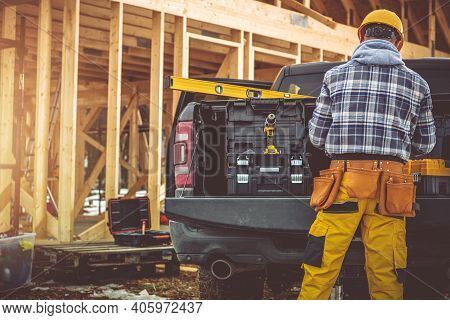 Caucasian Construction Contractor In His 40s And His Modern Black Pickup Truck. Men Preparing His To