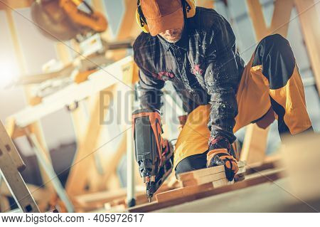 Woodwork Job. Caucasian Construction Worker In His 40s With Nail Gun In His Hand. Wooden House Frame