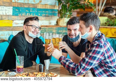 Happy Young Friends With Face Mask Drinking Beer At Restaurant Table After Reopening - Smiling Men H