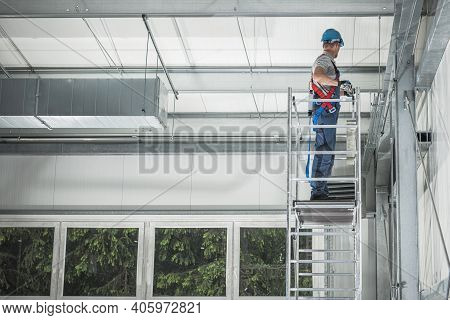 New Steel Warehouse Building And Interior Finishing By Caucasian Worker In His 40s On Aluminium Scaf