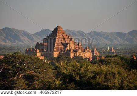 Bagan, Myanmar - November 18, 2015: Ancient Oriental Temple In Green Terrain, View Of Beautiful Ston