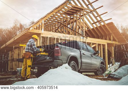 Contractor Worker In Yellow Hard Hat Preparing For His Shift Next To His Pickup Truck. Residential H
