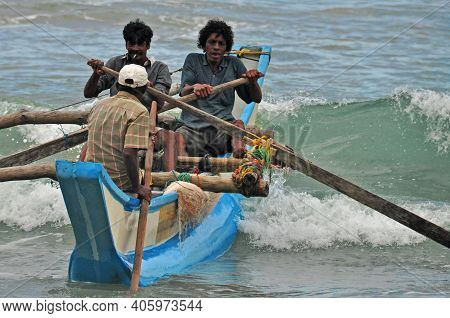 Hikkaduwa, Sri Lanka - 18 December 2011 Group Of Ethnic Men Sailing On Wooden Authentic Boat Rowing