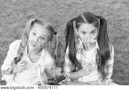 Ready For Party. Little Children Hold Mustache Props Green Grass. Small Girls With Photobooth Props