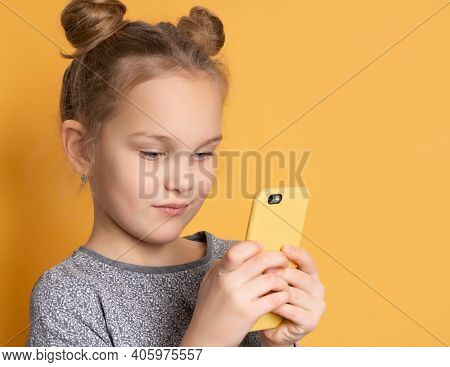 Close Up Of A Concentrated Little Girl Looking At Her Smartphone While Standing On A Pink Background