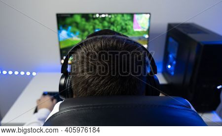 The Guy Is Playing An Online Game. Gamer Sits At A Computer In A Blue Neon Room